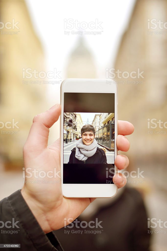 Hand holding phone with lady's image as she has photo taken stock photo