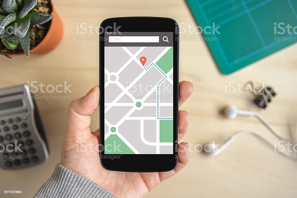 Hand holding phone with map gps navigation application on screen stock photo