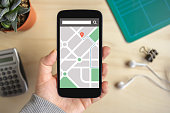 Hand holding phone with map gps navigation application on screen