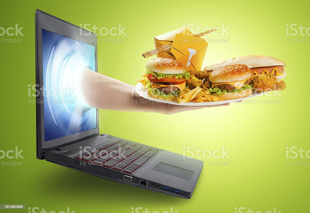 Hand holding plate with food coming out of laptop screen stock photo