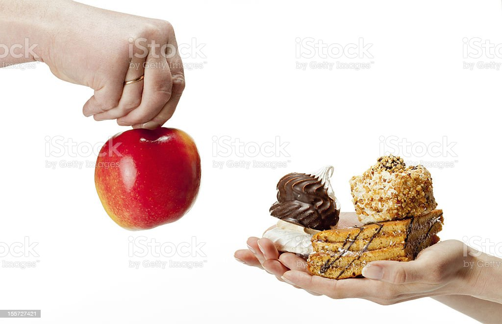 Hand holding red apple and another hand holding desserts royalty-free stock photo