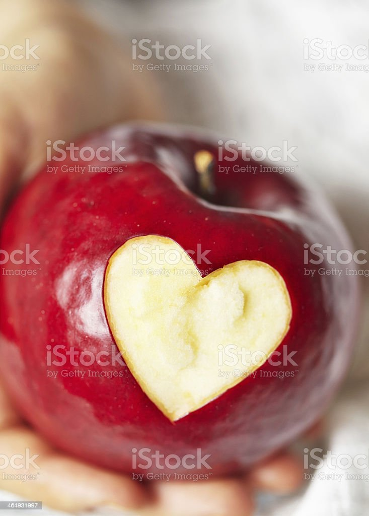 Hand holding red apple with heart stock photo