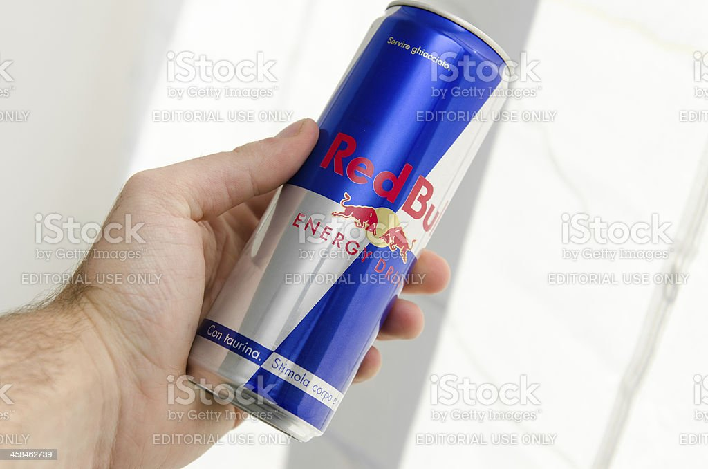 Hand holding Red Bull Cans stock photo
