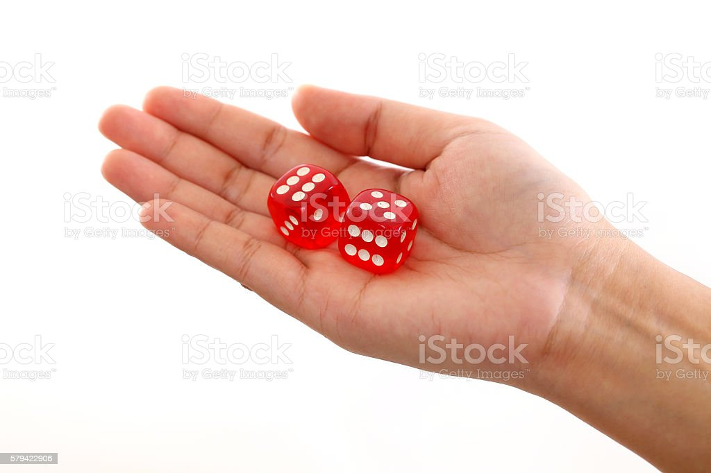 Hand holding red dice against white background stock photo