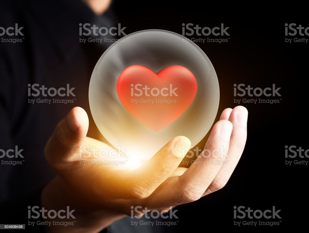 Hand holding red heart in crystal ball,Insurance concept stock photo