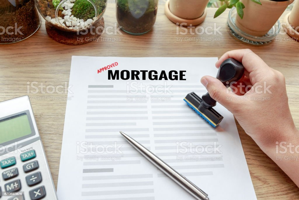 Hand holding rubber stamp with mortgage document, pen and calculator. stock photo