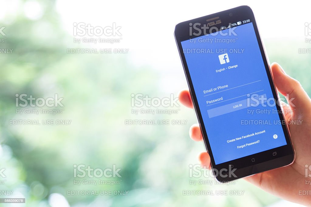hand holding screen shot of Facebook application stock photo