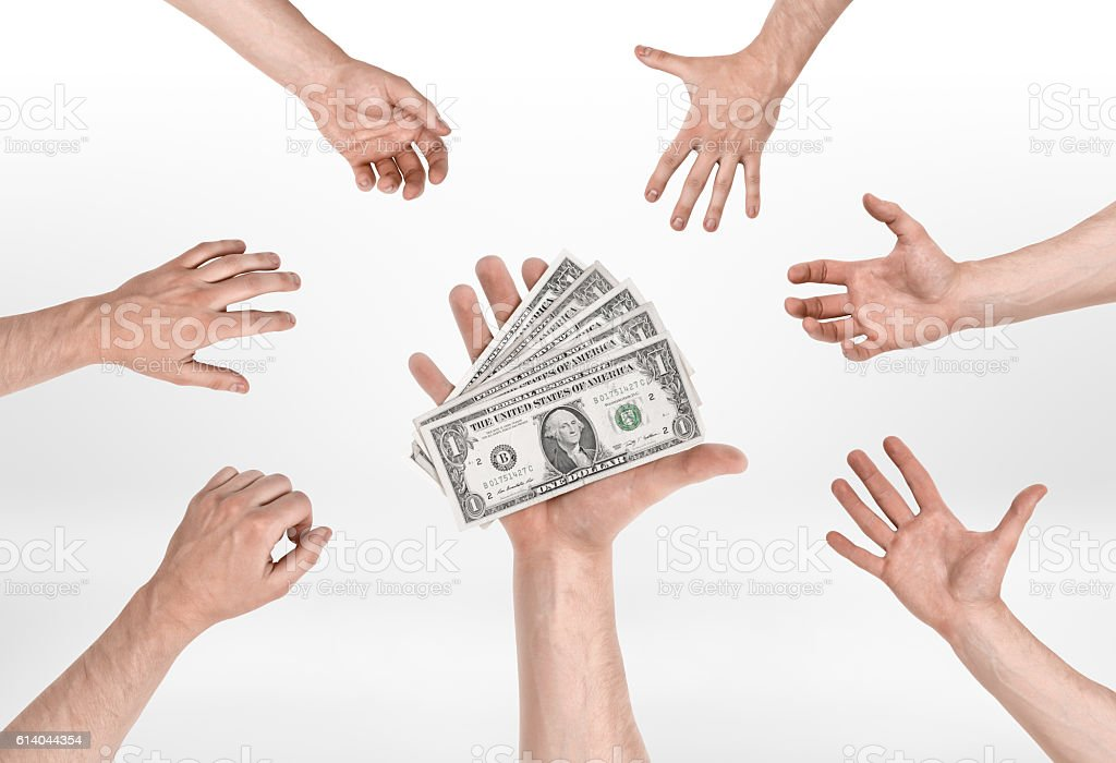 Hand holding several dollar bills and other hands trying to stock photo