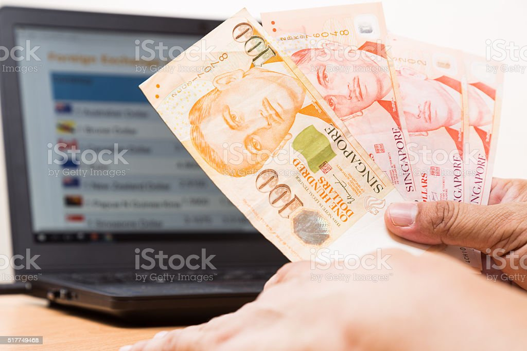 Hand holding Singapore dollar in office with computer in background stock photo