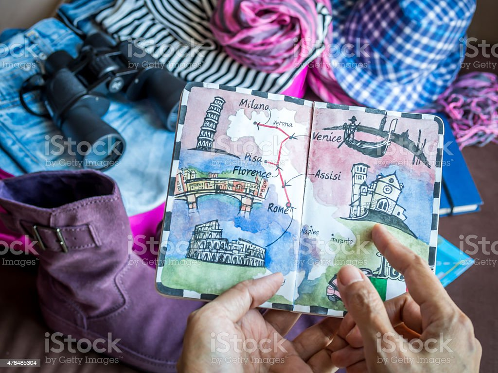 Hand holding sketch book illustration over  luggage stuff scattered background stock photo