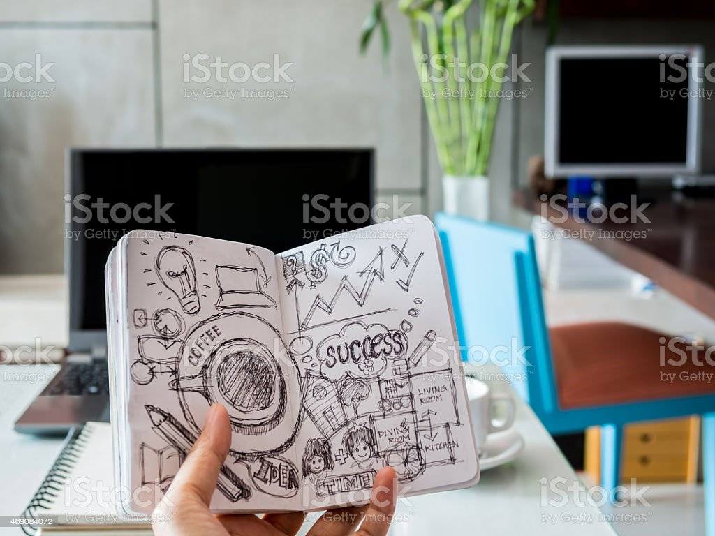 Hand holding sketch book over modern workspace background stock photo