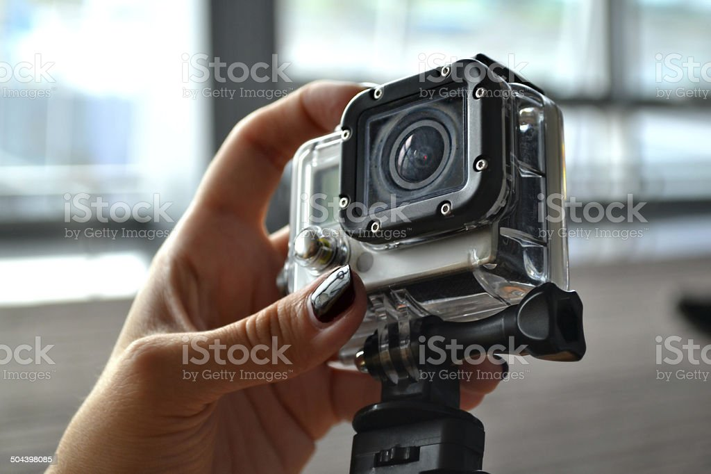 Hand holding small camera in waterproof covering stock photo