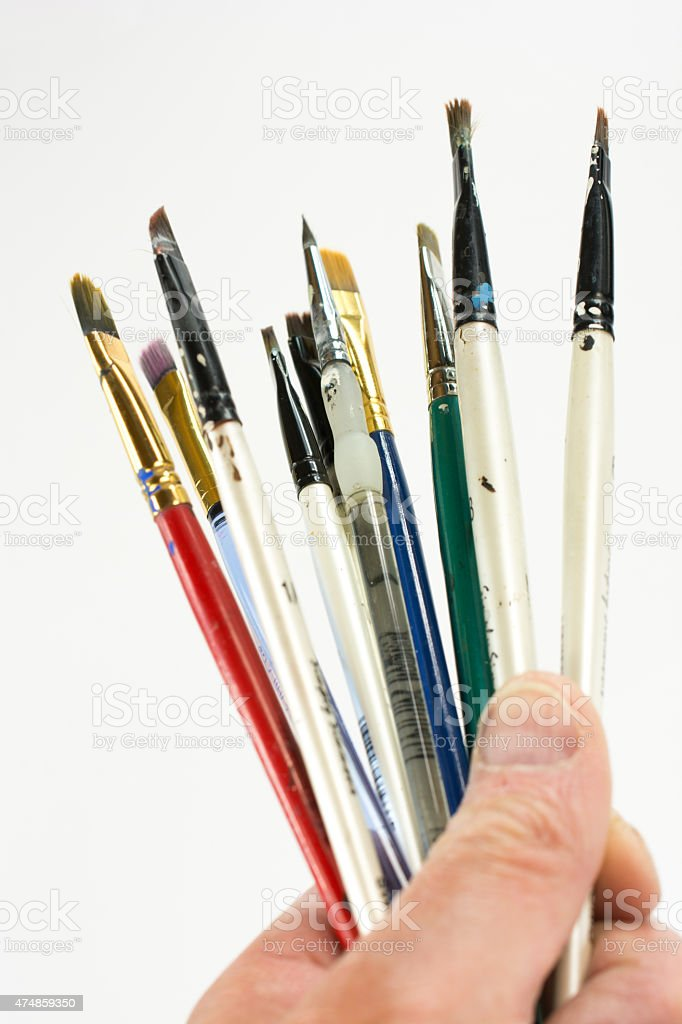 Hand holding small paint brushes against a white background stock photo