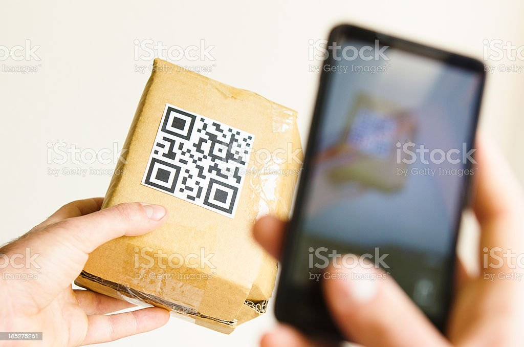 Hand holding smart phone and checking price with QR stock photo