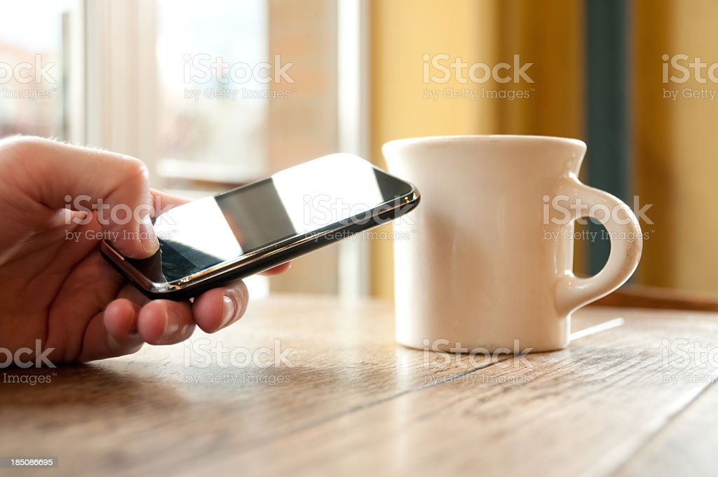 Hand holding smart phone next to white mug on wooden table royalty-free stock photo