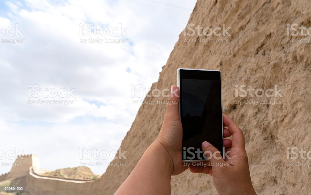 Hand holding smart phone, taking pictures of ancient fortress stock photo