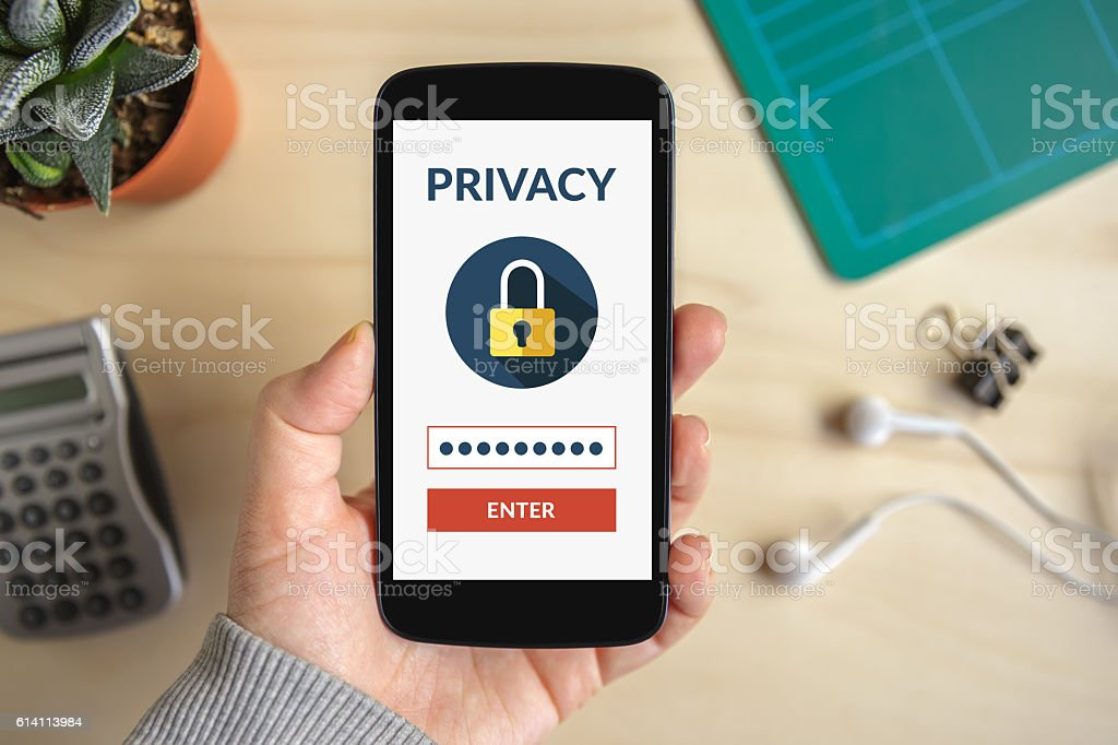 Hand holding smart phone with online privacy concept on screen stock photo