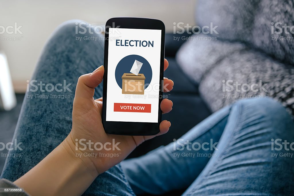 Hand holding smart phone with online voting concept on screen stock photo