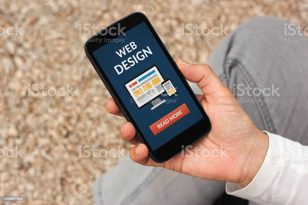 Hand holding smart phone with web design concept on screen stock photo