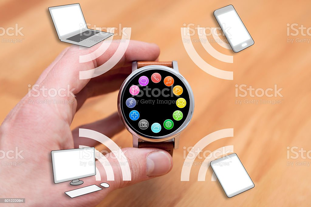 Hand Holding Smart Watch Connected to Devices stock photo