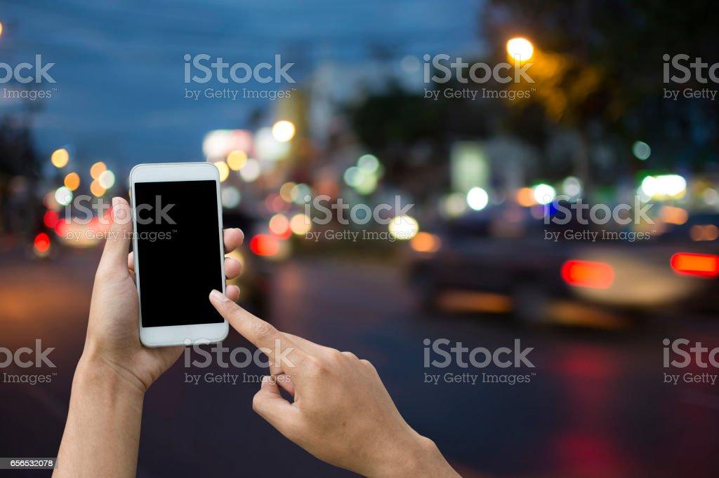 Hand holding smartphone on blur background transport. stock photo