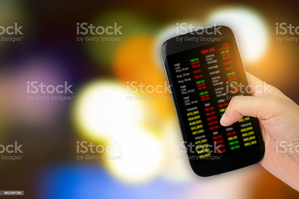Hand holding smartphone on colorful abstract blurred background stock photo