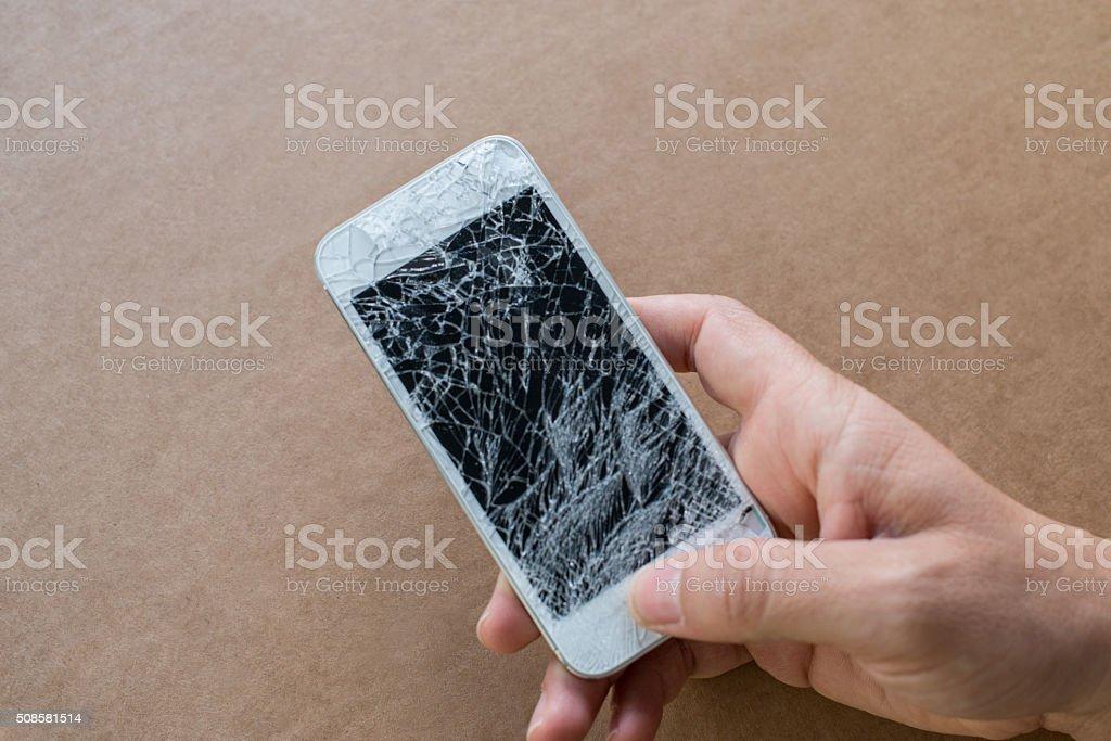 Hand holding smartphone with broken screen stock photo