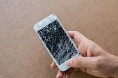 Hand holding smartphone with broken screen