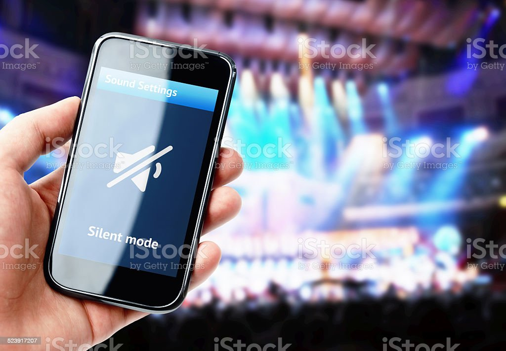 Hand holding smartphone with mute sound during concert stock photo