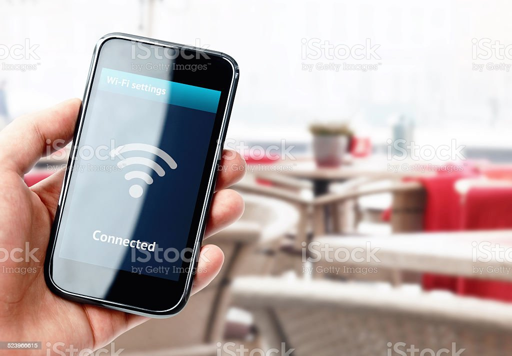 Hand holding smartphone with wi-fi connection in cafe stock photo