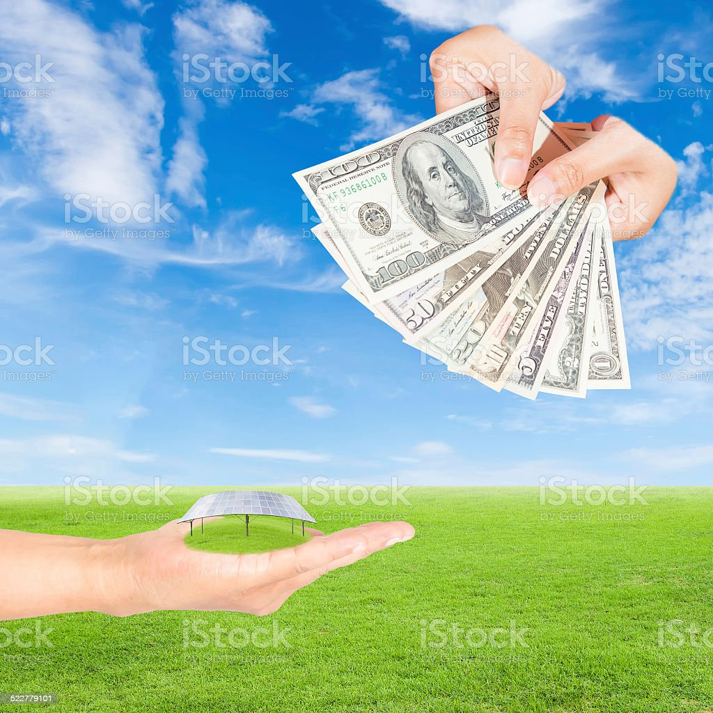 hand holding solar panels and US Dollars banknote stock photo