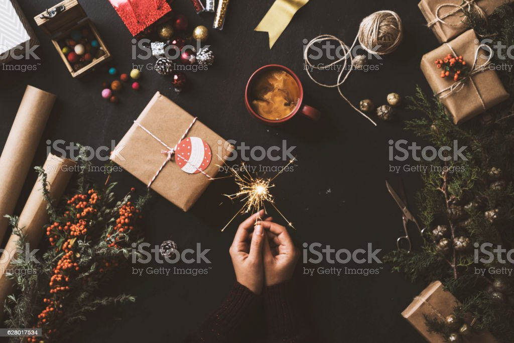 Hand holding sparkler with sparks, Christmas preparations on table stock photo