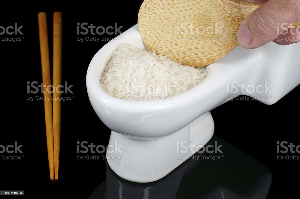 Hand Holding Spatula Into a Toilet Bowl of Rice royalty-free stock photo