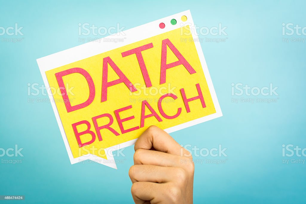 Hand holding speech bubble with 'Data Breach' words. Security concept. stock photo