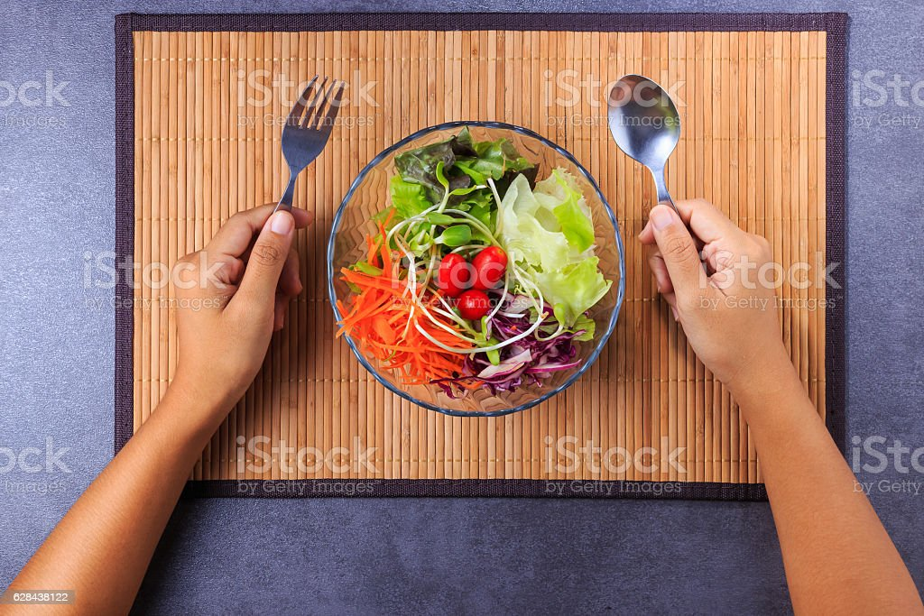 Hand holding spoon and fork with fresh salad bowl stock photo