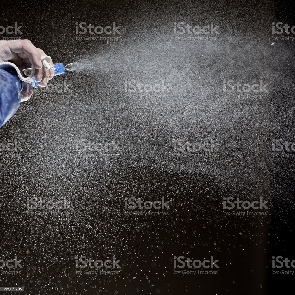 hand holding spray bottle and spraying water stock photo
