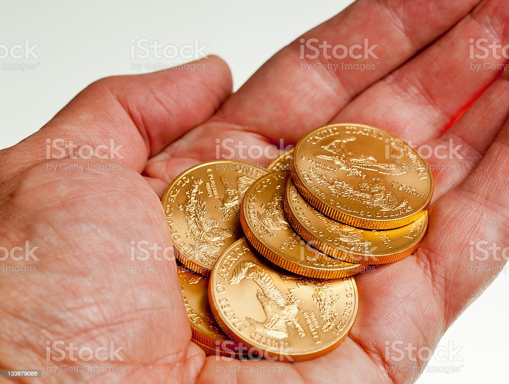 Hand holding stack of gold coins stock photo