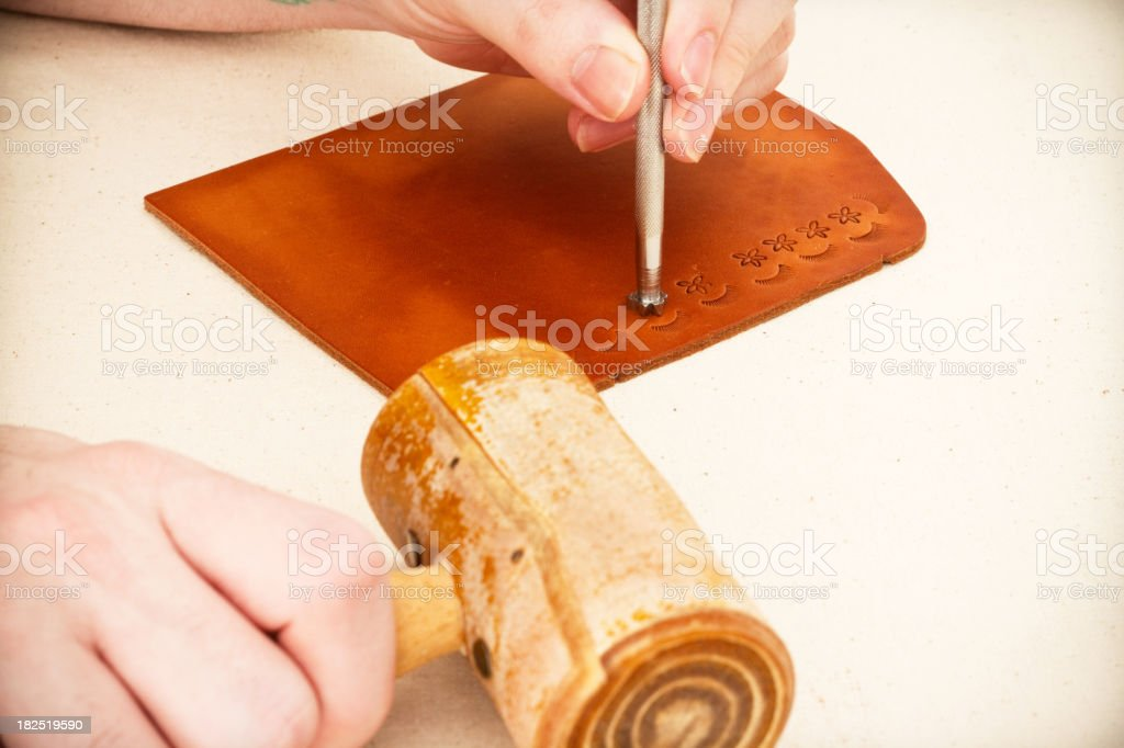 Hand holding stamping tool making shapes in piece of leather royalty-free stock photo