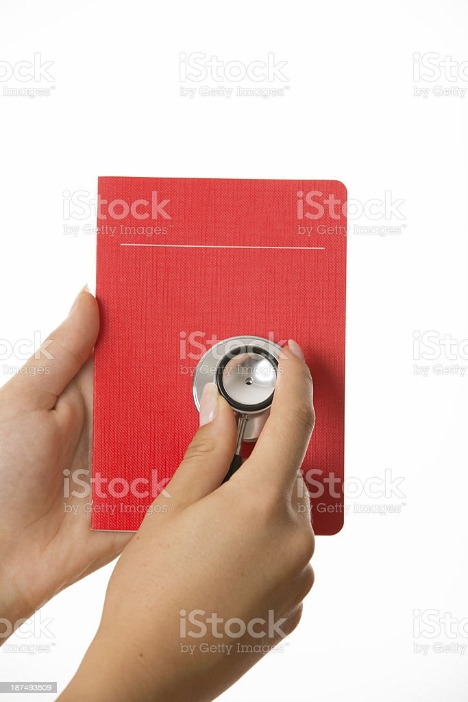 Hand holding stethoscope on red savings book stock photo