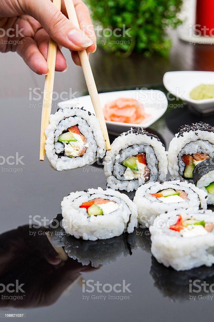 Hand holding stick with maki sushi set royalty-free stock photo
