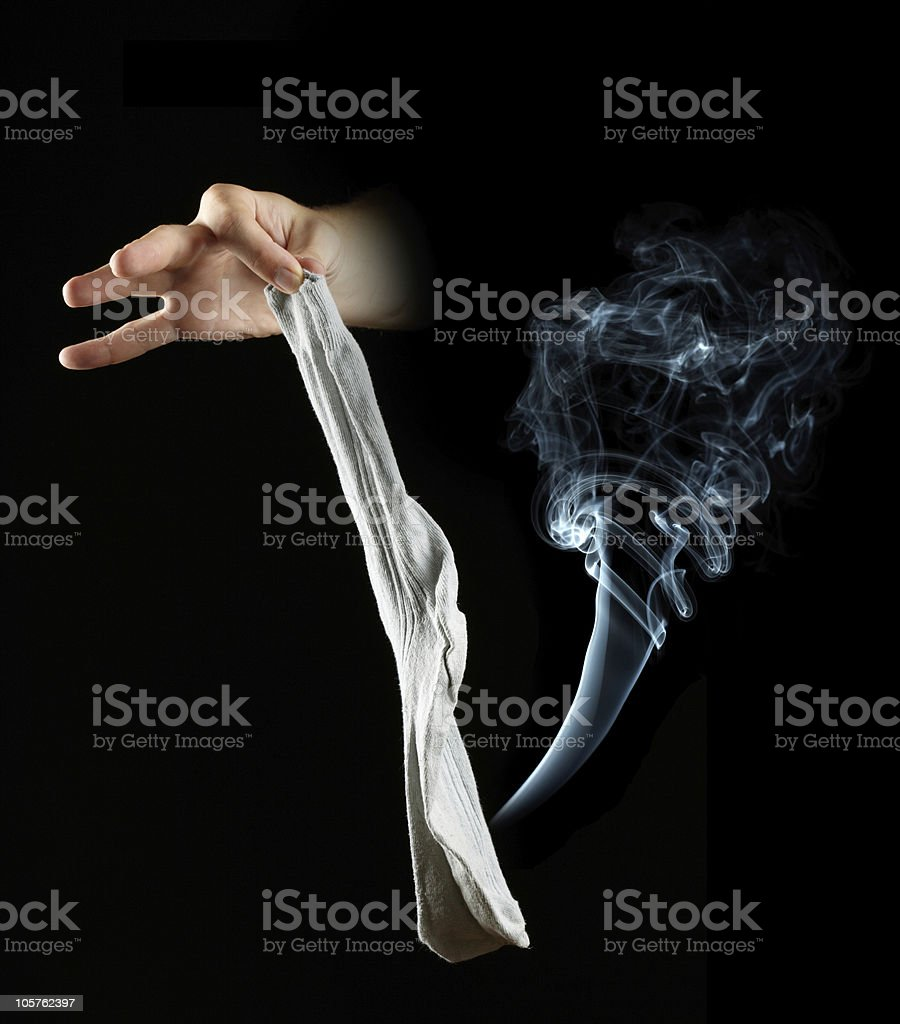 Hand holding stinky sock on black background royalty-free stock photo