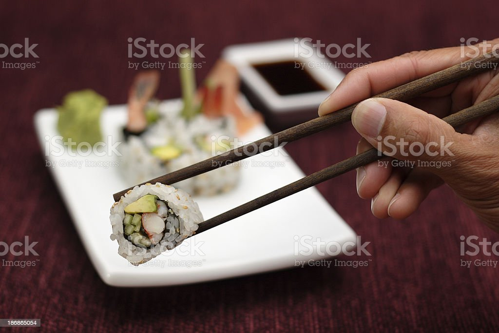 Hand Holding Sushi with Chopsticks royalty-free stock photo
