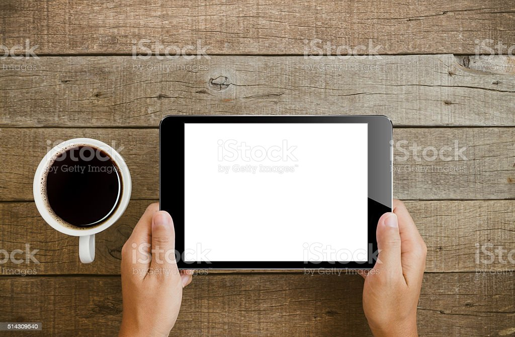 hand holding tablet on wood table stock photo