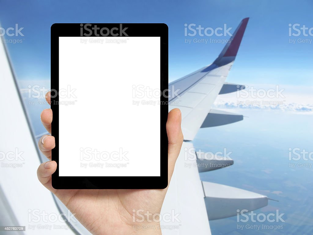 Hand holding tablet PC in an airplane royalty-free stock photo