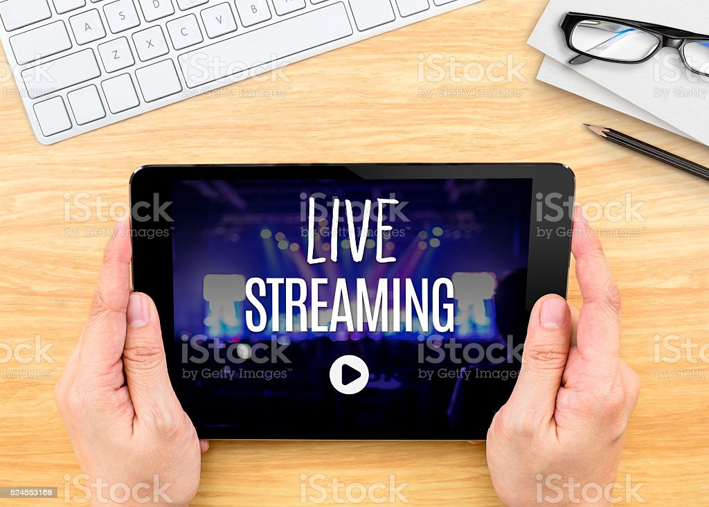 Hand holding tablet with Live Streaming word on table stock photo