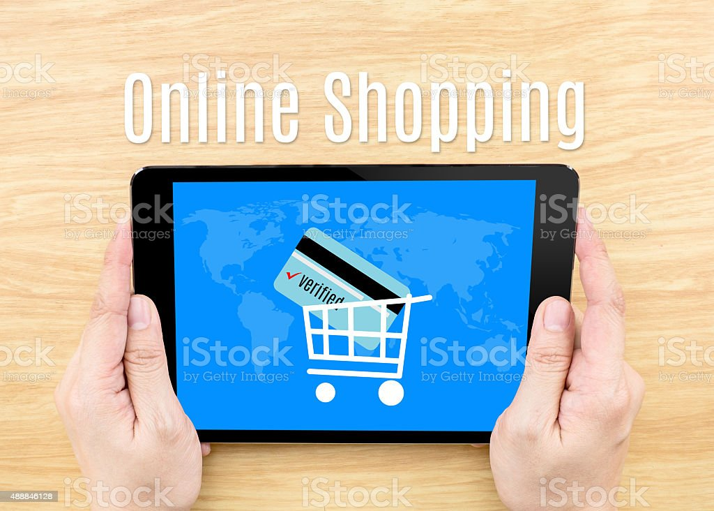 Hand holding tablet with Online shopping word on wooden table stock photo