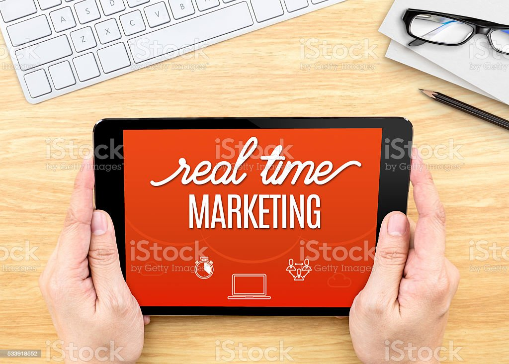 Hand holding tablet with Real-time marketing word on wood table stock photo
