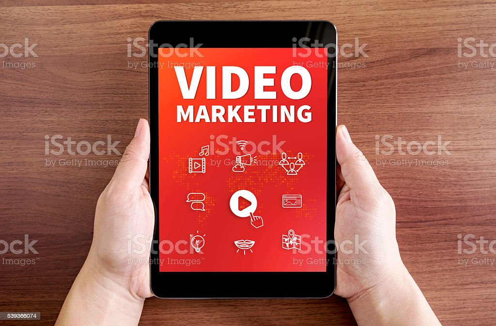 hand holding tablet with Video marketing and icon on screen stock photo