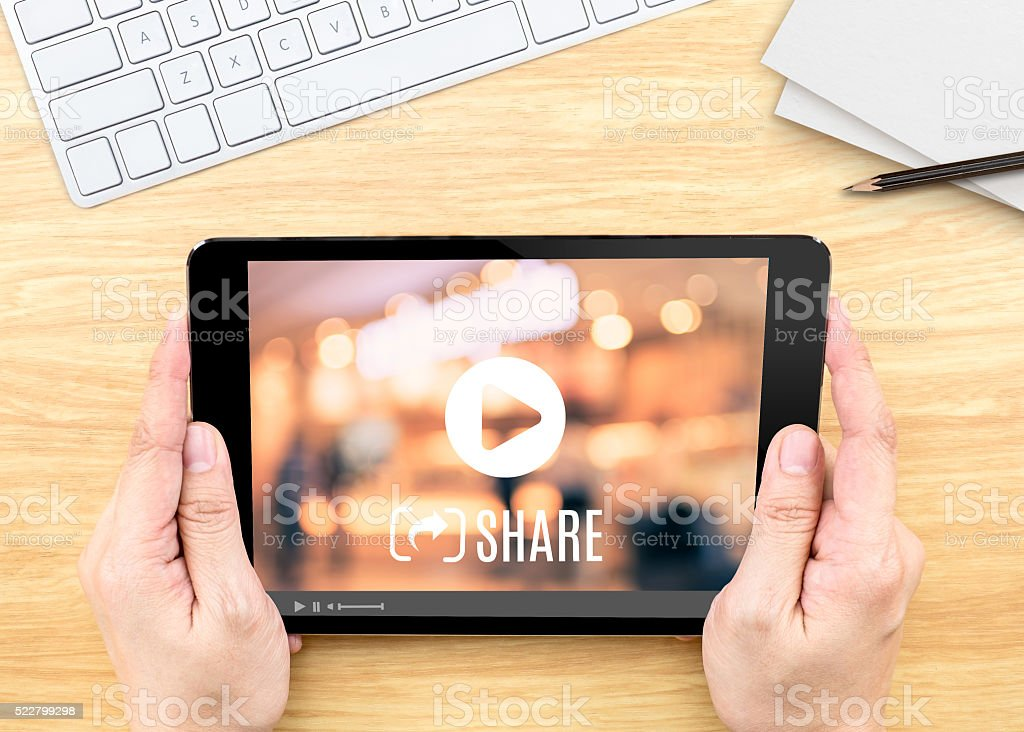 Hand holding tablet with Video sharing on screen on table stock photo