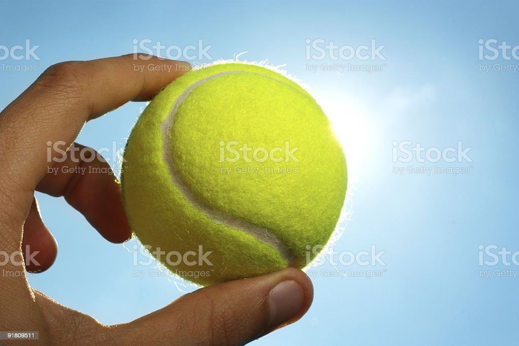 Hand holding tennis ball up to the sky royalty-free stock photo